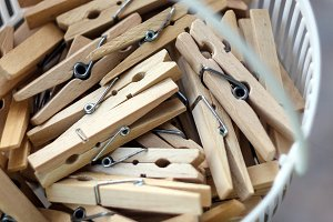 Wooden clothespins in the basket, bl