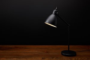 close up view of black lamp on woode