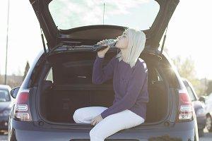 woman sitting in car trunk. car trav