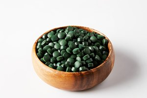 wooden bowl with pile of spirulina p