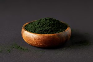 spirulina algae powder in wooden bow