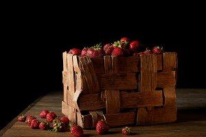 ripe strawberries in rustic box on w