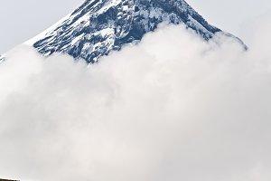 Snowy rocky volcano cone in clouds
