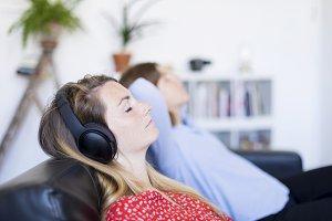 Woman listening to headphones in liv