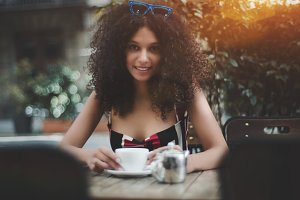 Charming curly lady in street bar