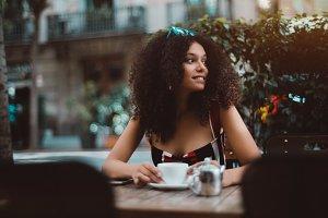 Beautiful curly woman in street bar