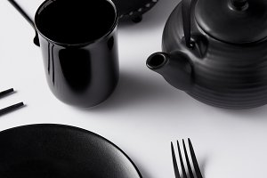close up view of black teapot, plate
