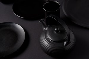 selective focus of black teapot, cup