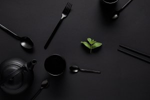 Top view of black teapot, chopsticks