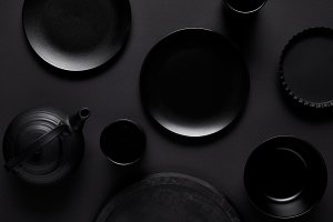 top view of black teapot, plates, bo