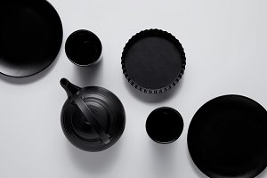 top view of black teapot, plates, ba