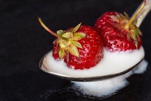 strawberry in yogurt on a dark backg