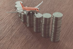 toy plane on stacks of coins on wood