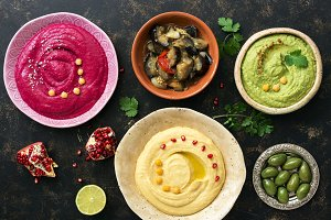 Colorful hummus in bowls on a dark