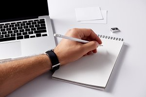 cropped shot of man writing in noteb