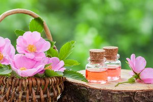 Rose hip flowers and oil bottles