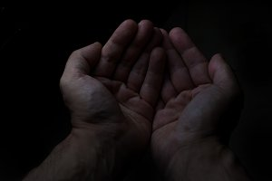 Two hands of  man in black backgroun