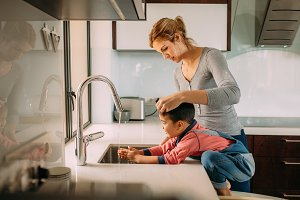 Caring mother and kid wash hands