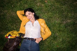 woman smiling lying on green grass