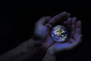 Two hands protect the earth globe. E