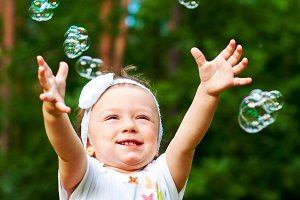 little girl reaching for bubbles