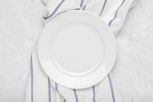 Clean white plate on towel