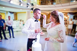 Fabulous young bride feeding cake to