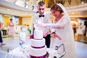 Wedding couple cutting their big whi