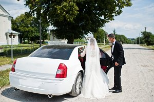 Groom holding the wedding car doors