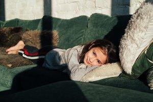 hipster child girl lying on sofa