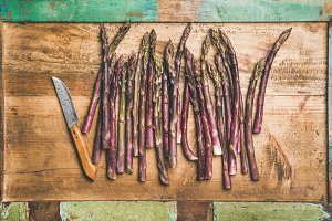 Fresh purple asparagus over wooden