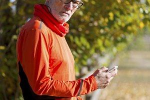 Senior runner man watching his smart