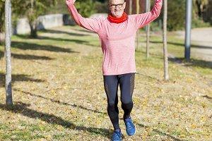 Senior runner man arms up after runn