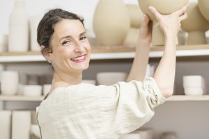 Ceramist woman holding a potter in h