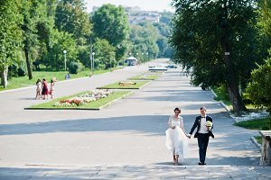 Attractive young wedding couple walk