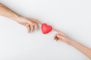 top view of hands touching red heart