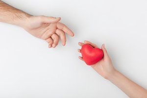 cropped view of hands with red heart