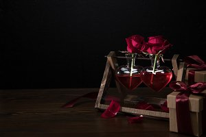 two red roses in heart shaped vases