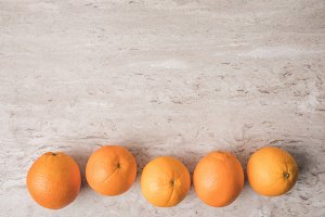 top view of row of oranges on marble