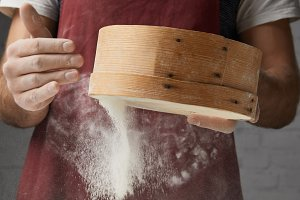 cropped image of chef sifting flour