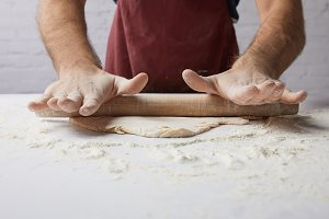 cropped image of chef rolling dough