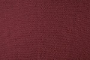 close up view of burgundy woven fabr