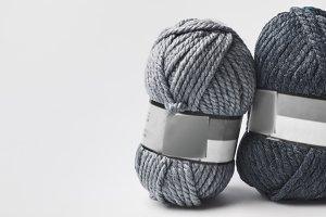 two grey yarn balls with blank tag i