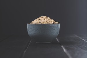 bowl of raw rice with spices on blac