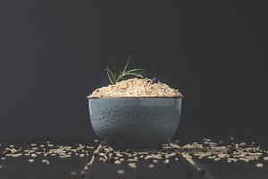 bowl of raw rice with rosemary and s