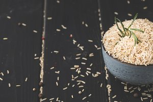 bowl of raw rice with rosemary on bl