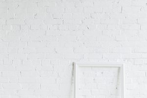 empty frame in front of white brick