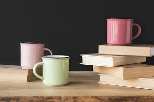 three colored cups and books on wood