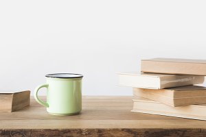 green cup and books on wooden table