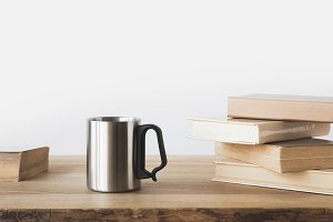 silver cup and books on wooden table